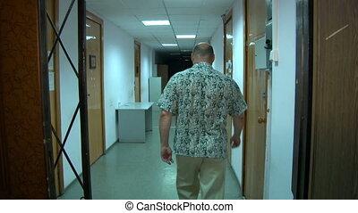 A man is walking along the corridor