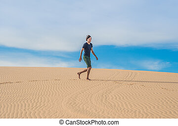 A man is walking in the desert Vietnam, Mui Ne.