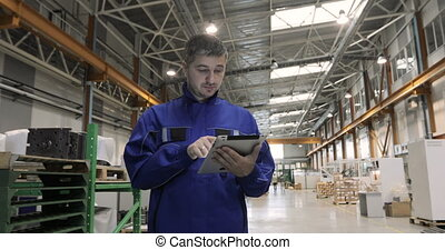 A man is working in a factory with a digital tablet, he is dressed in a blue uniform. factory worker.