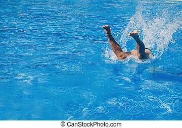a man jumps into the pool. Swimmer in the water
