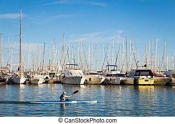 A man kayaking along rows of yachts at the Palma bay. Palma de Mallorca, Spain.