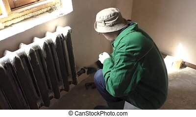 A man keeps a nut on a pipe iron radiator