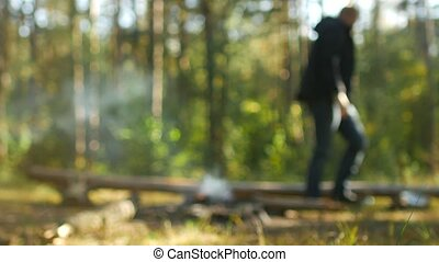A man kindles a fire in the woods in nature, outdoor...