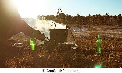 a man kindles firelit campfire hiker halt on a campsite...