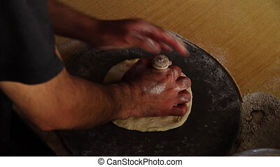 A man kneading the dough - A hand held, high angle, medium...