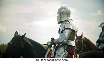 A man knight in the armor riding a horse - another knight...
