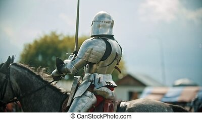 A man knight riding a horse around the battlefield and...
