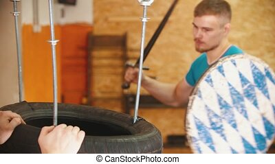 A man knight training on swords on the bunch of tires - another man holding the bundle. Mid shot