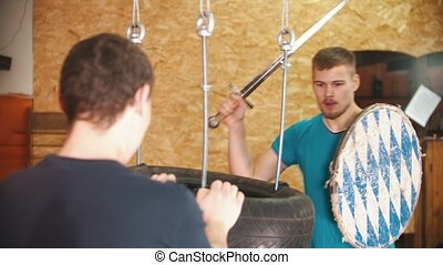 A man knight training on swords on the bunch of tires in the gym - another man holding the bundle. Mid shot