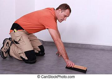 A man laying lino.