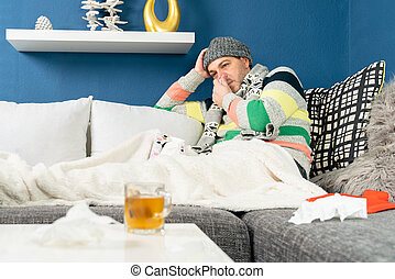 man lies sick on his couch at home