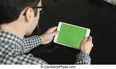 A Man Look a Horizontal Tablet at His Desk.