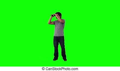 A man looking through binoculars is turning
