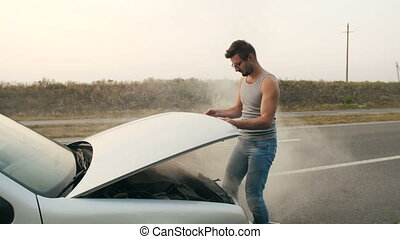 A man looks at a smoking engine of a broken car