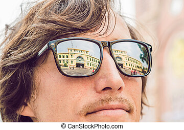 A man looks at Saigon Central Post Office on blue sky background in Ho Chi Minh, Vietnam. Steel structure of the gothic building was designed by Gustave Eiffel.