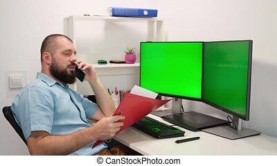 a man looks into a folder and speaks on the phone. yells at the interlocutor. a man working at home in front of two green monitors. remote work. employee emotions