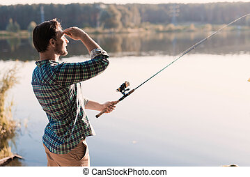 A man looks out on the river, holding a spinning rod in front of the river