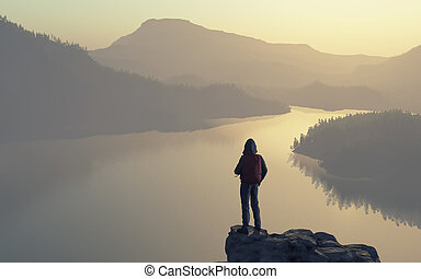 A man looks over the top of the mountain lake and forest.