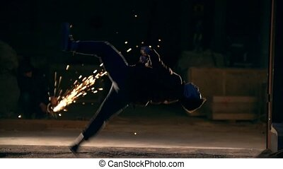 A man makes a flip in the air, tricks of martial arts in night city, slow-motion