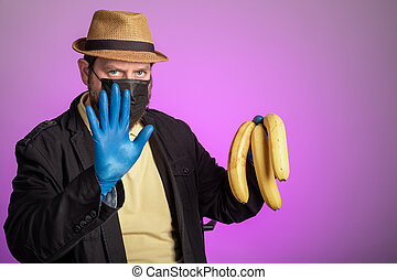 a man makes a gesture with his hand calls to stop, in the other hand bananas