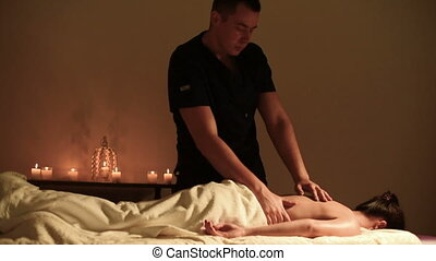 A man makes a massage to a young woman with his elbow. Dark key. Medium Shot