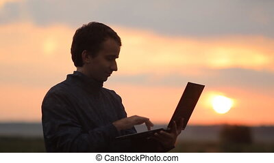 A man makes a video call on a laptop. Beautiful sunset on the background