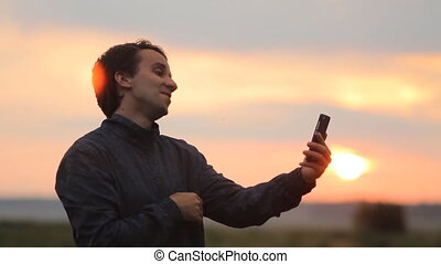 A man makes a video call on the phone. Beautiful sunset on the background