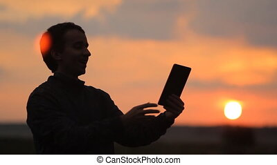 A man makes a video call on the tablet. Beautiful sunset on the background