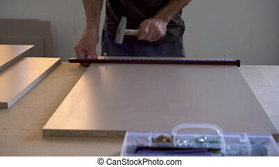 A man makes markings on wooden parts in a furniture ...