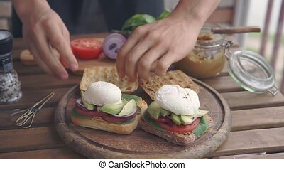 a man making sandwiches with poached egg