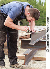 A man marks a metal product before cutting