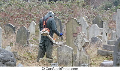 A man mowering the grasses in the cemetery
