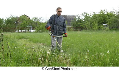 A man mows the grass near his country house.