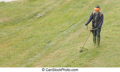 A man mows the grass with a mower, trimming