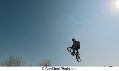 A man on a bicycle performing tricks in the skatepark....