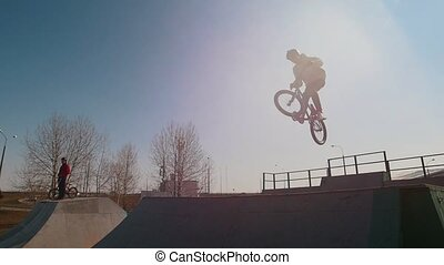 A man on a bicycle performing tricks in the skatepark. Jumps...