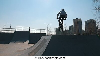 A man on a bicycle performing tricks in the skatepark. Urban...