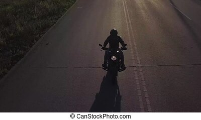 a man on a motorcycle rides on the road. The camera moves back to accompany the rider. Video from the drone.
