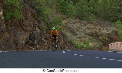 A man on a sports road bike rides on the road located high in the mountains