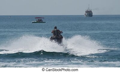 A man on a water motorcycle sails on the sea against the backdrop of a wave boat
