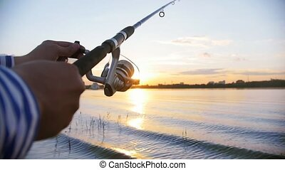 A man on fishing - spinning the coil on fishing rod - sunset. Mid shot
