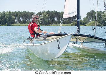 a man on his sailboat