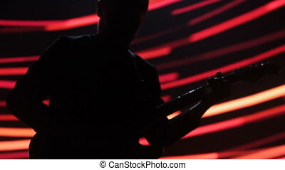 A man on stage plays electric guitar