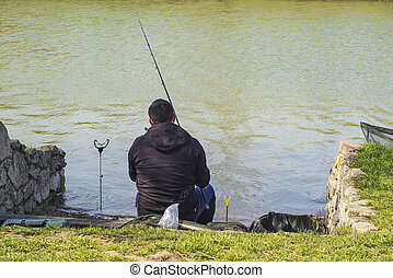 A man on the riverbank with a fishing rod catches a fish. Spring warm day man with fishing rod , man standing on the riverbank fishing fish.