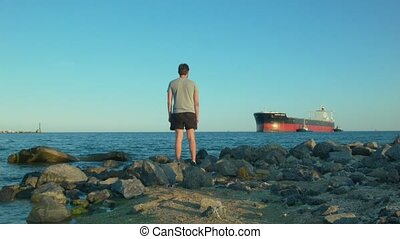 A man on the shore looks at a large ship sailing past.