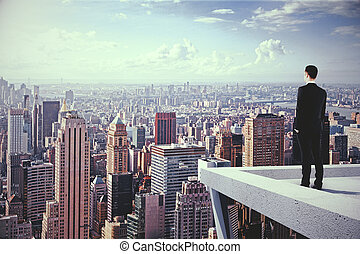 A man on the top of skyscrapeer looking at the city