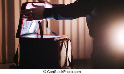 A man opening case with light in it and looking inside - A...