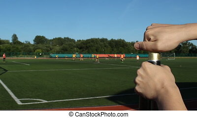 A man opens a bottle of beer on the background of a football field where they play football, close-up
