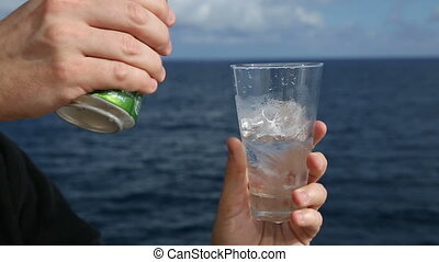 a man opens a can of soda on the ocean