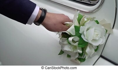A man opens the door of the wedding car. White retro car. The groom sits in the automobile